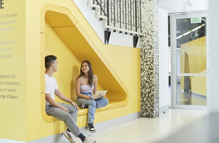 Two students sit in yellow interior of Business School