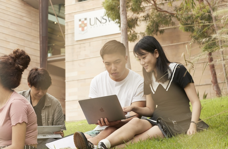 Two students sitting on UNSW main walkway